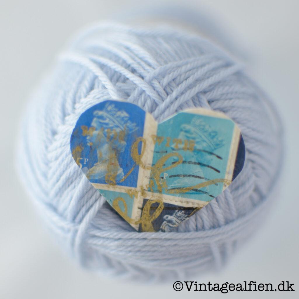 Babyblåt garn og et blåt hjerte af frimærker