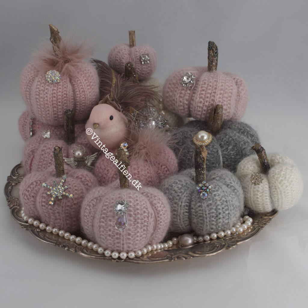 En samling af strikkede græskar fint pyntet med fjer og brocher