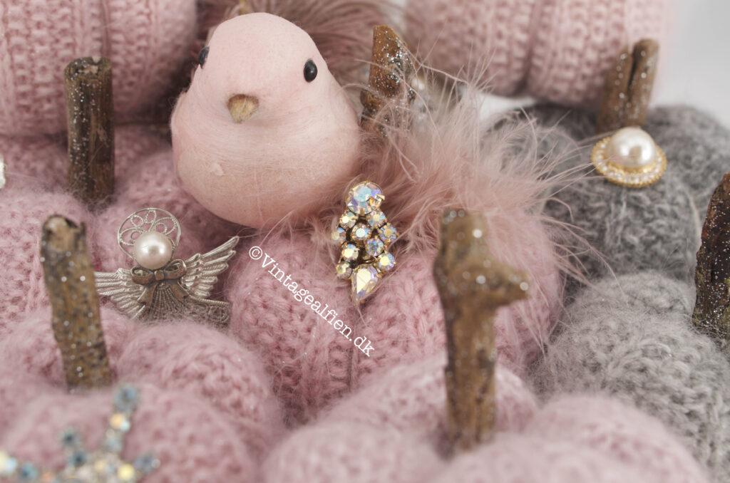 En pink julefugl er landet blandt en samling strikkede græskar