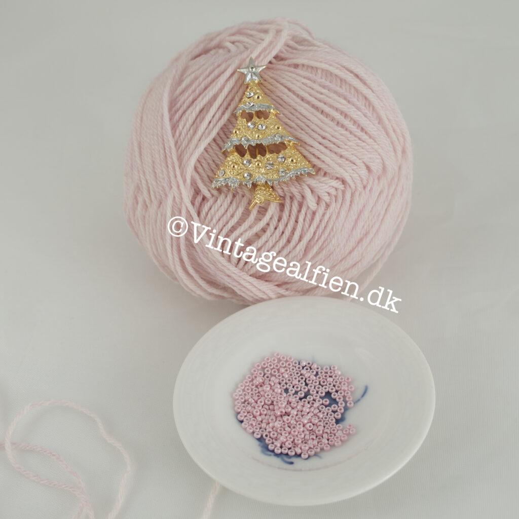 Perler i lyserød hældt op og klar til at blive strikket med