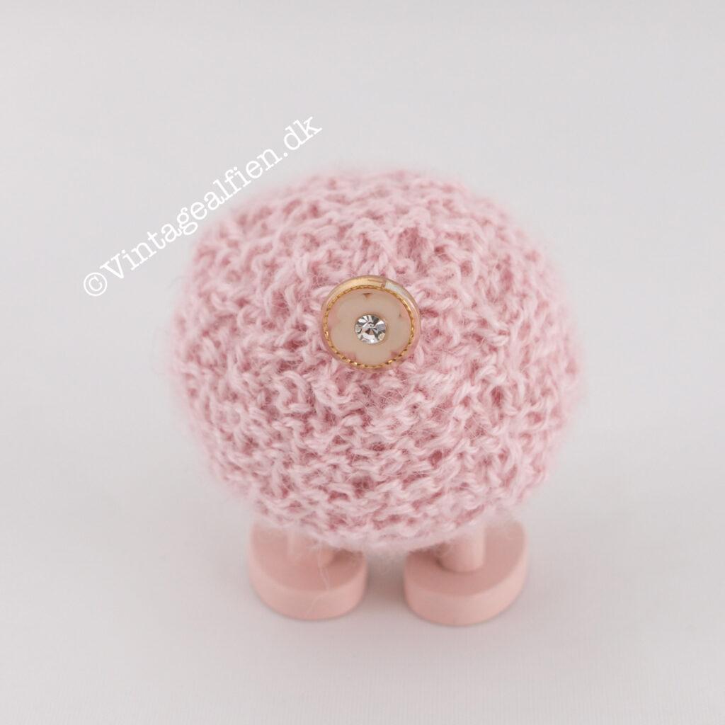 Miniaturestrik - den lille hoptimist set bagfra her med en lyserød baret