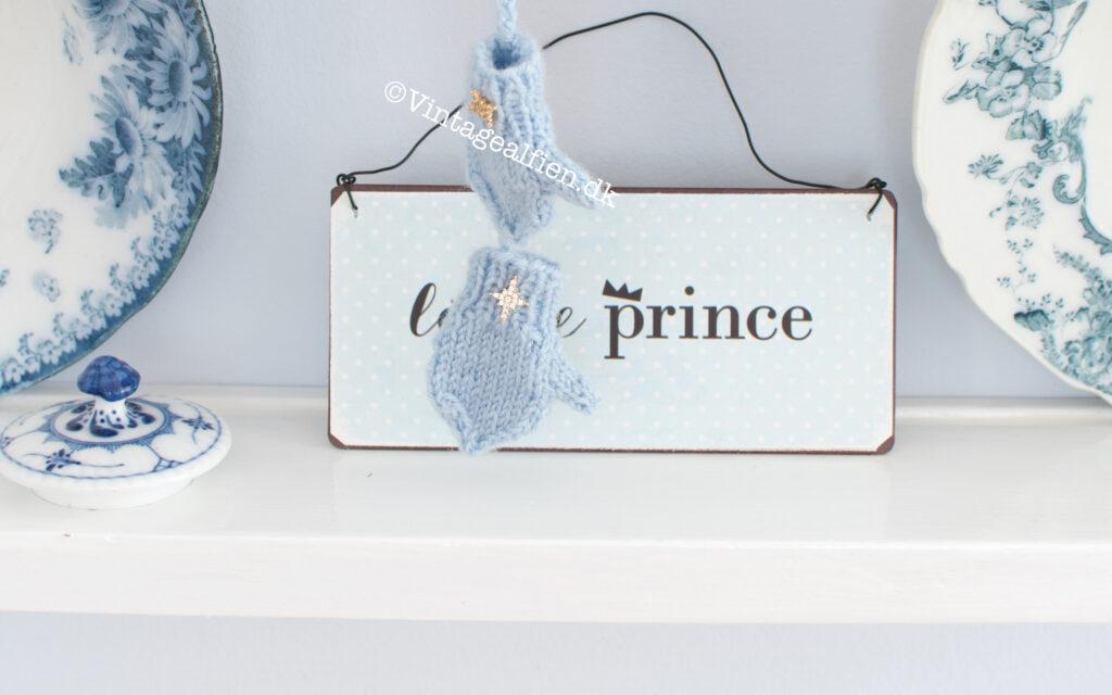 Miniaturestrik med et sæt små blå vanter der pynter på en tallerkenrække