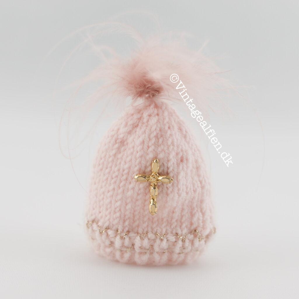 Miniaturestrik - strikket hue med pompom og kors