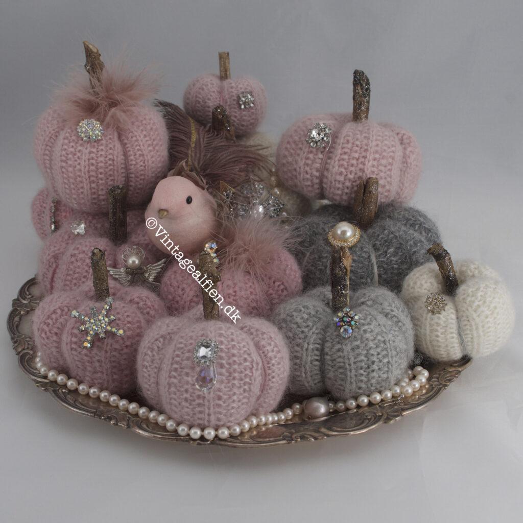 De strikkede græskar er pyntet op til jul med smykker og en pink fugl